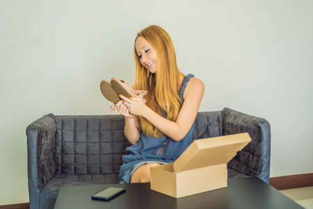 young woman received online shopping parcel opening boxes and buying fashion items by using credit card