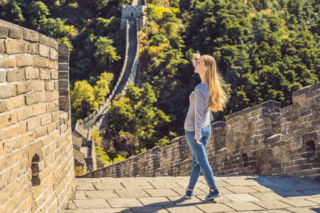 Happy cheerful joyful tourist woman at Great Wall of China having fun on travel smiling laughing and dancing during vacation trip in Asia. Girl visiting and sightseeing Chinese destination