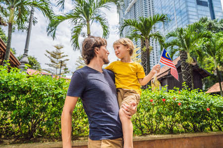 Father and son travelers in malaysia with malaysia flag celebrating the Malaysia independence day and Malaysia day. Travel to Malaysia concept