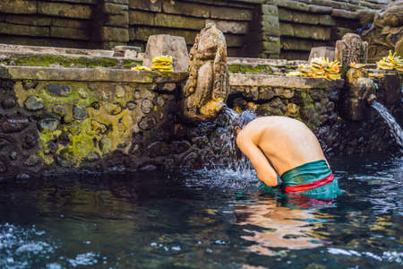 Man in holy spring water temple in bali. The temple compound consists of a petirtaan or bathing structure, famous for its holy spring water 免版税图像