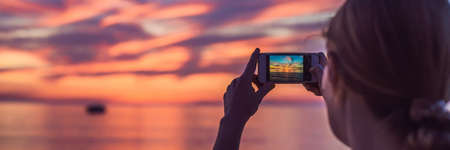Young asia woman selfie with mobile phone on a beach at sunset in summer, Phuket, Thailand. BANNER, LONG FORMAT