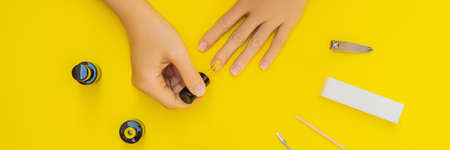 Woman Hands Care. Top View Of Beautiful Smooth Woman's Hands With Professional Nail Care Tools For Manicure On yellow Background. Closeup Of Healthy Female Nails With yellow Nail Polish. High Resolution. BANNER, LONG FORMAT Imagens
