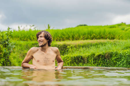 Man tourist in Belulang Hot Springs in Bali on the background of rice terraces