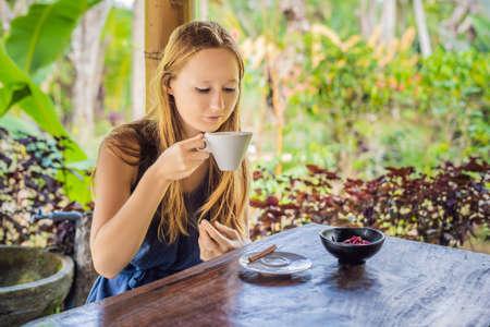 Young woman drinks coffee Luwak in the gazebo