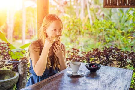 Young woman drinks coffee Luwak in the gazebo with sunlight