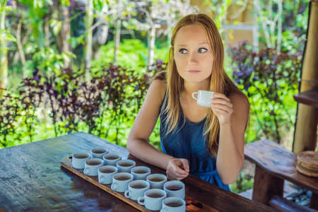 A young woman is tasting different kinds of coffee and tea, including coffee Luwak Stock Photo