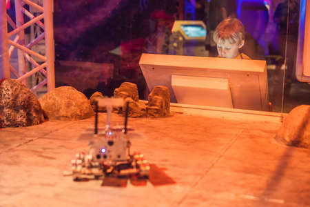 The boy controls the toy rover on Mars. Flight to Mars concept 写真素材