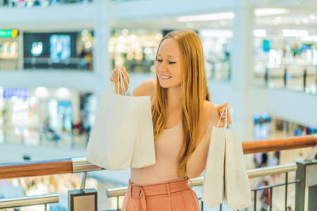 Women carrying a lot of shopping bags in blurred shopping mall