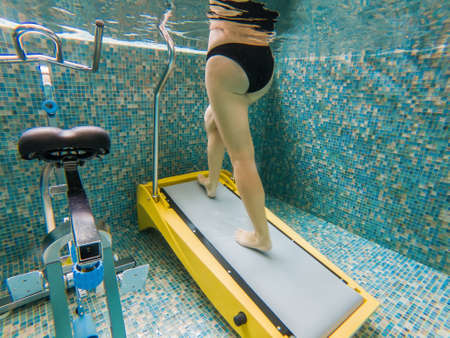 Young woman jogging on an underwater treadmill