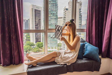 Woman sits by the window and uses an electronic hairbrush