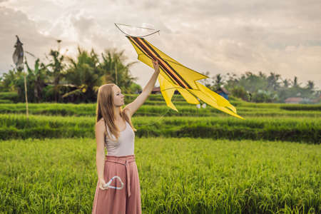 Young woman launches a kite in a rice field in Ubud, Bali Island, Indonesia