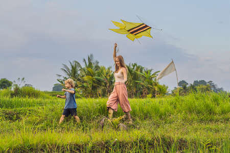 Mom and son launch a kite in a rice field in Ubud, Bali Island, Indonesia