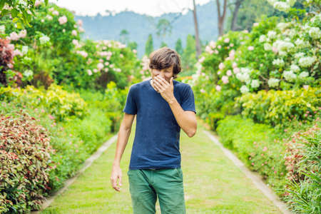 Young man blowing nose in front of blooming tree. Spring allergy concept Stock Photo