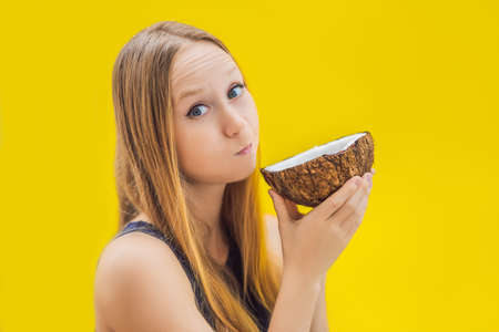 Young woman doing oil pulling over yellow