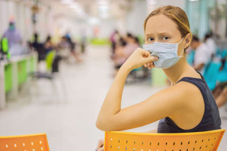Young woman sitting in hospital waiting for a doctors appointment. Patients In Doctors Waiting Room