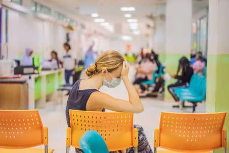 Jonge vrouw die in het ziekenhuis zit te wachten op een doktersafspraak. Patiënten in de wachtkamer van artsen