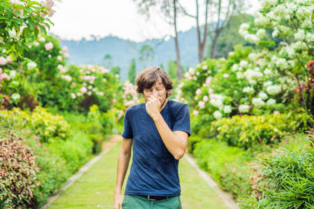 Young man blowing nose in front of blooming tree. Spring allergy concept Stock fotó