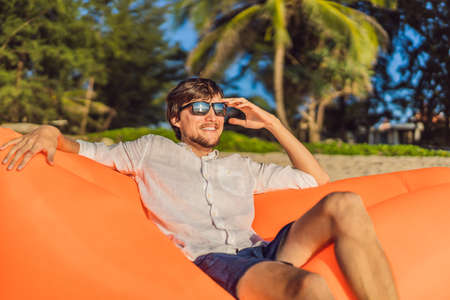 Summer lifestyle portrait of man sitting on the orange inflatable sofa on the beach of tropical island. Relaxing and enjoying life on air bed