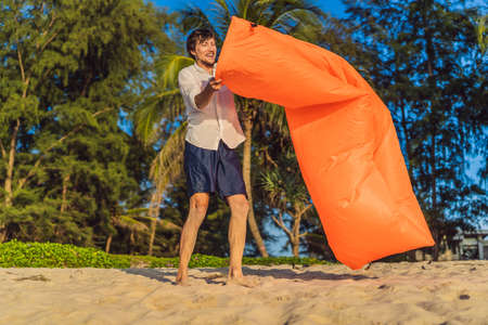 Summer lifestyle portrait of man inflates an inflatable orange sofa on the beach of tropical island. Relaxing and enjoying life on air bed