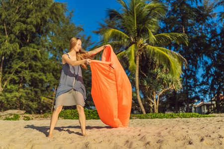 Summer lifestyle portrait of woman inflates an inflatable orange sofa on the beach of tropical island. Relaxing and enjoying life on air bed Banco de Imagens