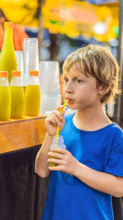 Boy drinking sugar cane juice on the Asian market VERTICAL FORMAT for mobile story or stories size. Mobile wallpaper