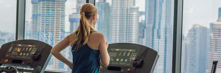 sport, fitness, lifestyle, technology and people concept - woman exercising on treadmill in gym against the background of a big city. BANNER, LONG FORMAT