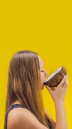 Young woman doing oil pulling over yellow background. VERTICAL FORMAT for mobile story or stories size. Mobile wallpaper Stock Photo