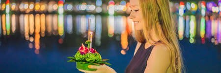 Young woman celebrates Loy Krathong, Runs on the water. Loy Krathong festival, People buy flowers and candle to light and float on water to celebrate the Loy Krathong festival in Thailand BANNER, LONG FORMAT