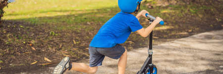 Boy riding scooters, outdoor in the park, summertime. Kids are happy playing outdoors BANNER, LONG FORMAT