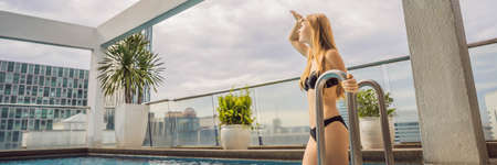 Young woman in the pool among the skyscrapers and the big city. Relax in the big city. Rest from stress BANNER, LONG FORMAT Stock Photo