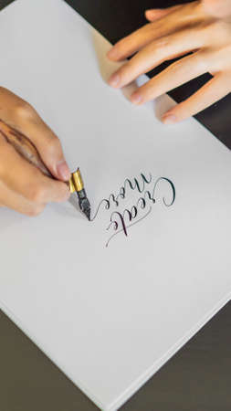Calligrapher hands writes phrase on white paper. Phrase - Create more. Inscribing ornamental decorated letters.