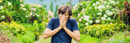 Young man blowing nose in front of blooming tree. Spring allergy concept BANNER, LONG FORMAT Stock Photo