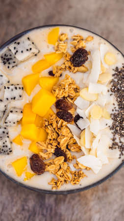 Smoothie bowls made with mango, banana, granola, grated coconut, dragon fruit, chia seeds and mint on wooden background.