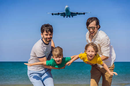 Two dads and two sons have fun on the beach watching the landing planes. Traveling on an airplane with kids concept. Text space. Island Phuket in Thailand. Impressive paradise. Hot beach Mai Khao. Amazing landscape Banco de Imagens