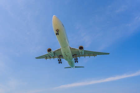 A white airplane flying in a clear pale blue sky Stock Photo