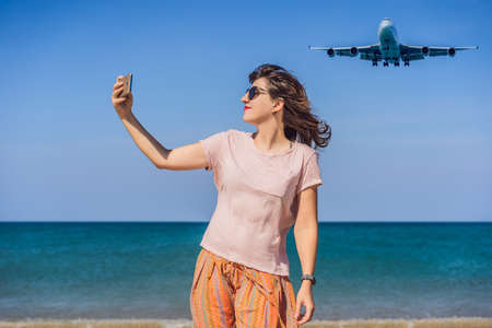 Woman makes a selfie on the beach watching the landing planes. Traveling on an airplane concept. Text space. Island Phuket in Thailand. Impressive paradise. Hot beach Mai Khao. Amazing landscape 版權商用圖片 - 120057268