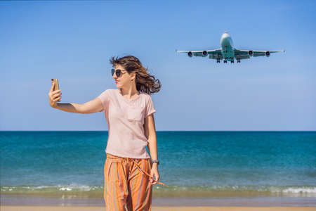 Woman makes a selfie on the beach watching the landing planes. Traveling on an airplane concept. Text space. Island Phuket in Thailand. Impressive paradise. Hot beach Mai Khao. Amazing landscape