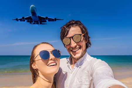 Man and woman tourists have fun on the beach watching the landing planes. Traveling on an airplane concept. Text space. Island Phuket in Thailand. Impressive paradise. Hot beach Mai Khao. Amazing landscape 版權商用圖片 - 120042693