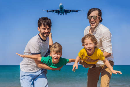 Two dads and two sons have fun on the beach watching the landing planes. Traveling on an airplane with kids concept. Text space. Island Phuket in Thailand. Impressive paradise. Hot beach Mai Khao. Amazing landscape