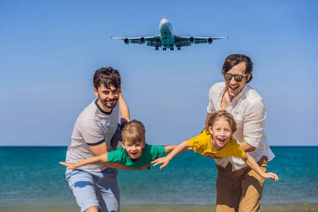 Two dads and two sons have fun on the beach watching the landing planes. Traveling on an airplane with kids concept. Text space. Island Phuket in Thailand. Impressive paradise. Hot beach Mai Khao. Amazing landscape 版權商用圖片