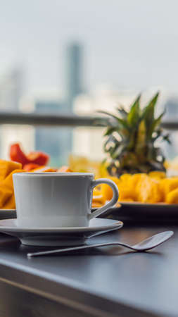 Breakfast table with coffee fruit and bread croisant on a balcony against the backdrop of the big city VERTICAL FORMAT for mobile story or stories size. Mobile wallpaper