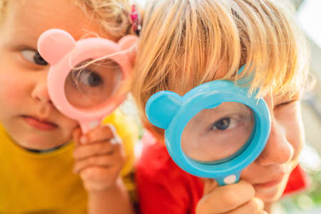 Boy and girl are looking in a magnifying glass against the background of the garden. Home schooling
