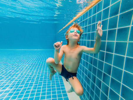 Underwater Young Boy Fun in the Swimming Pool with Goggles. Summer Vacation Fun