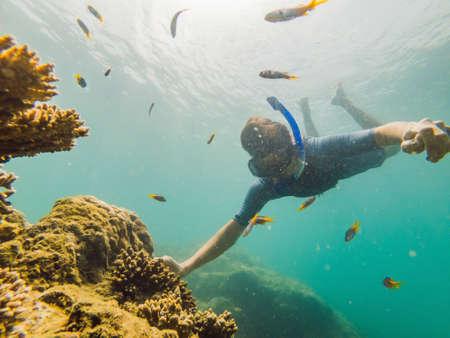Giovani uomini che fanno snorkeling esplorando il paesaggio sottomarino della barriera corallina nell'oceano blu profondo con pesci colorati e vita marina