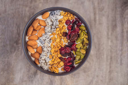 Mango smoothies bowl with almond, dragon fruit, dried cherries, pumpkin seeds and granola on wooden background.