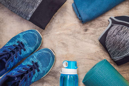 Everything for sports turquoise, blue shades on a wooden background. Yoga mat, sport shoes sportswear and bottle of water. Concept healthy lifestyle, sport and diet. Sport equipment. Copy space.