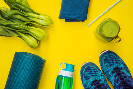 Everything for sports turquoise, blue shades on a yellow background and spinach smoothies. Yoga mat, sport shoes sportswear and bottle of water. Concept healthy lifestyle, sport and diet. Sport equipment. Copy space 스톡 콘텐츠