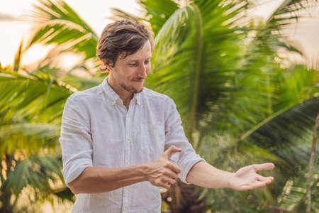 Junger Mann sprüht Mückenschutzmittel im Wald, Insektenschutz Standard-Bild