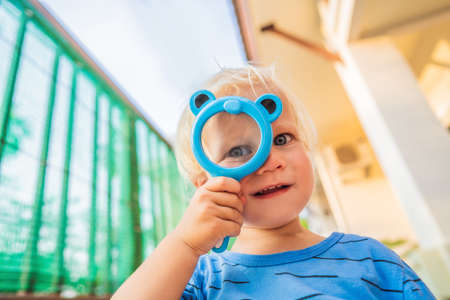 Boy looking in a magnifying glass against the background of the garden. Home schooling Stock Photo
