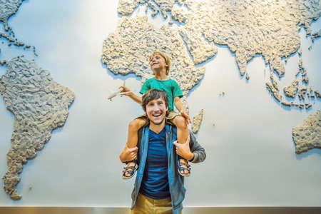 Dad and son on the background of a world map with an airplane in his hands. Travel concept
